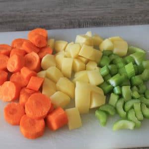 Tagliare a pezzettoni il sedano, le patate e le carote